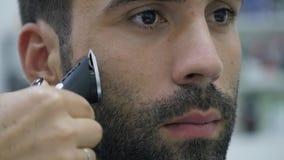 Hairstylingsproces Close-up van een kappers drogend haar van een jonge gebaarde mens stock videobeelden