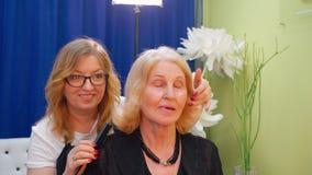 Hairstylist που κάνει hairstyle για την ξανθή ώριμη γυναίκα στο σαλόνι ομορφιάς Hairstyling τρίχα στιλίστων ομορφιάς της ανώτερης φιλμ μικρού μήκους