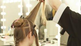 Hairstylist που κτενίζει την τρίχα σκελών και που ψεκάζει το νερό πρίν κόβει στο σαλόνι ομορφιάς Κλείστε επάνω την παραγωγή κομμω απόθεμα βίντεο