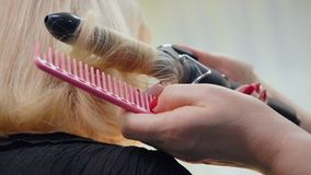 Hairstylist που χρησιμοποιεί τις λαβίδες τρίχας για να κατσαρώσει τα ξανθά μαλλιά του προτύπου ομορφιάς κοντά επάνω φιλμ μικρού μήκους