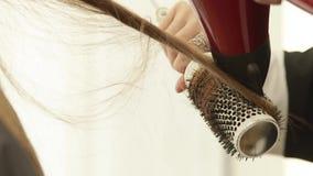 Hairstylist που χρησιμοποιεί το στεγνωτήρα για την ξήρανση μακρυμάλλη και τη βούρτσα γηα τα μαλλιά για τον προσδιορισμό μετά από  φιλμ μικρού μήκους