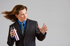 Hairstylist. A portrait of a handsome long-haired man in suit holding a bottle of hair spray Stock Images