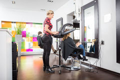 Hairstylist Adjusting Drying Accelerator Over Customer's Head stock photography