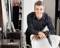 Hairstylist With Blower Leaning On Chair Stock Image