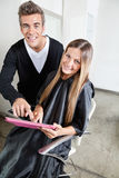 Hairstylist With Client Using Digital Tablet Royalty Free Stock Image