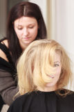 Hairstylist combing female client blond girl in hairdressing salon Royalty Free Stock Photography