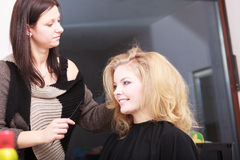 Hairstylist combing female client blond girl in hairdressing salon Stock Photo