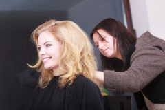Hairstylist combing female client blond girl in hairdressing salon Stock Images