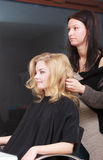 Hairstylist combing female client blond girl in hairdressing salon Royalty Free Stock Images