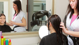 Hairstylist combing hair woman client in hairdressing beauty salon Royalty Free Stock Image