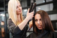 Hairstylist curling hair woman client in hairdressing beauty salon Stock Images