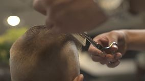 Hairstylist cutting hair with barber scissors and comb in hairdressing salon close up. Children haircut with hair stock footage