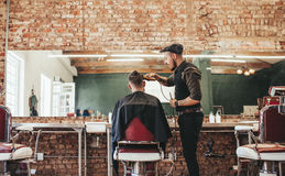 Hairstylist cutting hair of male customer. At barber shop. Barber serving client, making haircut using hair clipper Stock Photography
