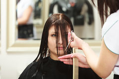 Hairstylist cutting hair woman client in hairdressing beauty salon stock photos