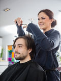 Hairstylist Cutting Male Client's Hair In Salon royalty free stock photo