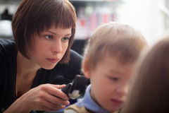 Hairstylist cutting a young boys hair Royalty Free Stock Image