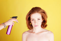 Hairstylist, der Haar-Spray anwendet Lizenzfreie Stockbilder