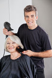 Hairstylist With Dryer Setting Up Woman's Hair. Portrait of male hairstylist with dryer setting up senior woman's hair in beauty parlor royalty free stock image