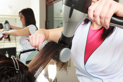 Hairstylist drying hair woman client in hairdressing beauty salon Stock Photos