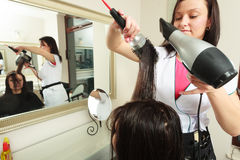 Hairstylist drying hair woman client in hairdressing beauty salon Royalty Free Stock Photos