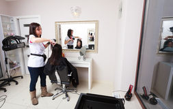 Hairstylist drying hair woman client in hairdressing beauty salon Stock Image