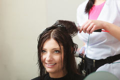 Hairstylist drying hair woman client in hairdressing beauty salon Stock Photography