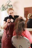 Hairstylist drying teenager hairs Stock Photography