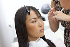 Hairstylist giving a haircut to Asian woman Royalty Free Stock Images