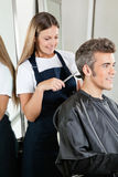 Hairstylist Giving Haircut To Client At Salon Stock Photo