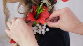 Hairstylist, hairdresser finishing creative hairstyle with flowers for teen girl stock video footage