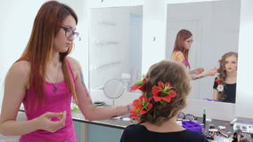 Hairstylist, hairdresser finishing creative hairstyle with flowers for teen girl stock footage