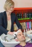 Hairstylist hairdresser washing customer hair. Head royalty free stock photography