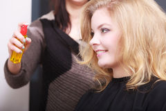 Hairstylist hairspray and client in hair salon Royalty Free Stock Photos