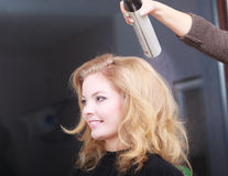Hairstylist with hairspray client in hair salon Stock Photos