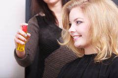 Hairstylist with hairspray and female client blond girl in salon Royalty Free Stock Images