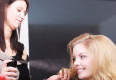 Hairstylist with hairspray and female client blond girl in salon Stock Photo