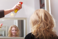 Hairstylist with hairspray and female client blond girl in salon royalty free stock photo