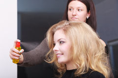 Hairstylist with hairspray and female client blond girl in salon Stock Images