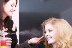 Hairstylist with hairspray and female client Stock Images