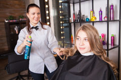 Hairstylist with hairspray and female client Royalty Free Stock Images
