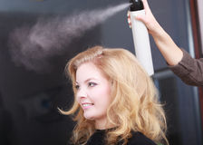 Hairstylist with hairspray and female client in hair salon Royalty Free Stock Image