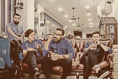 Hairstylist and his staff on a break time. Portrait of a hairstylist with his staff sitting on a couch on their break time at his barber shop - focus on the royalty free stock photography