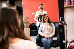 Hairstylist holding mirror and shows to customer a new of hair. Hairstylist holding mirror and shows to customer a new style of hair stock images