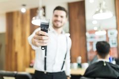 Hairstylist Holding Trimmer With Focus On Hand In Salon. Young male hairstylist holding trimmer with focus on hand in salon Royalty Free Stock Photography