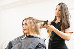 Hairstylist ironing some hair. Good looking young hairstylist using a hair straightener on a woman`s hair in a salon Stock Photo