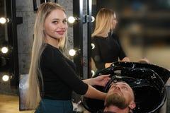 Hairstylist klienta ` s p?uczkowy w?osy w fryzjera m?skiego sklepie fotografia royalty free