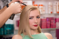 Hairstylist makes hairstyle for beautiful girl Royalty Free Stock Photos