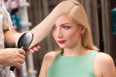 Hairstylist makes hairstyle for beautiful girl Stock Image