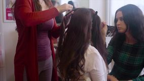 Hairstylist making hair-do while make up artist applying eyeshadows slow motion. stock video footage