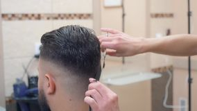 Hairstylist making modern hairdo with scissor and comb, close shot. Males nape close-cropped. Recorded in barbershop. Interior of hairdressing saloon stock video